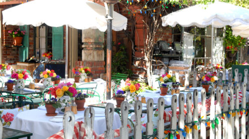 Quaint cafe with lots of colorful floral arrangements and cute white picket fence