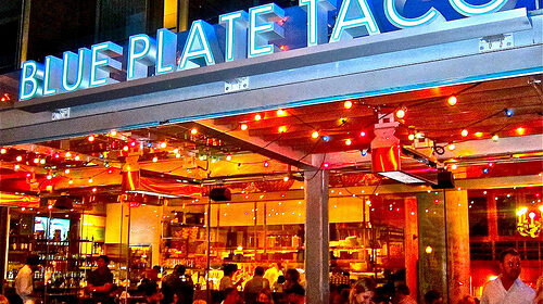 Nitetime view of people dinning outside of restaurant