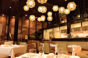 Upscale restaurant open room with white table linens and eclectic lighting above.