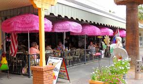 Exterior of building with tables,chairs and pink table umbrellas
