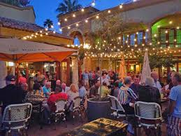 Outside tables and chairs with string lights overhead