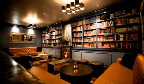 Bench seating ,small round tables and wall of books
