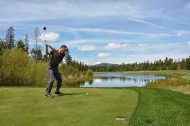 Golfer swinging view grass water mountains